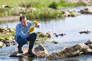 Environmental Health - man testing water in a stream